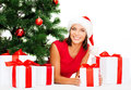 Smiling woman in santa helper hat with gift boxes christmas x mas winter happiness concept many and tree Royalty Free Stock Images
