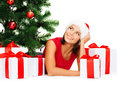 Smiling woman in santa helper hat with gift boxes christmas x mas winter happiness concept many and tree Stock Images