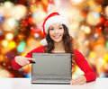 Smiling woman in santa helper hat with laptop christmas holidays technology advertisement and people concept pointig finger to Stock Images