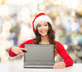 Smiling woman in santa helper hat with laptop christmas holidays technology advertisement and people concept pointig finger to Royalty Free Stock Images