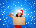 Smiling woman in santa helper hat with parcel box christmas x mas winter happiness concept Stock Photography