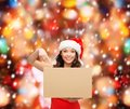 Smiling woman in santa helper hat with parcel box christmas x mas winter happiness concept Royalty Free Stock Image