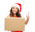 Smiling woman in santa helper hat with parcel box christmas x mas winter happiness concept showing thumbs up Royalty Free Stock Image