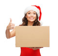 Smiling woman in santa helper hat with parcel box christmas x mas winter happiness concept showing thumbs up Stock Photos