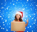 Smiling woman in santa helper hat with parcel box christmas x mas winter happiness concept showing thumbs up Stock Photo