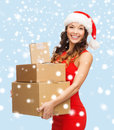 Smiling woman in santa helper hat with parcels christmas x mas winter happiness concept many parcel boxes Stock Photo