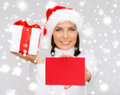 Smiling woman in santa helper hat with postcard christmas x mas valentine s day celebration concept gift box and Royalty Free Stock Images