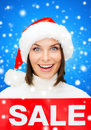 Smiling woman in santa helper hat with sale sign shopping christmas holidays and people concept red over blue snowy Stock Image