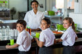 Smiling woman with schoolchildren in canteen Royalty Free Stock Photo