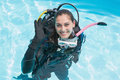 Smiling woman on scuba training in swimming pool making ok sign a sunny day Royalty Free Stock Photography