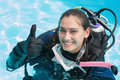 Smiling woman on scuba training in swimming pool showing thumbs up a sunny day Stock Photo