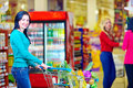 Smiling woman shopping at supermarket with trolley pretty women Royalty Free Stock Images