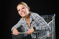 Smiling woman in shopping trolley Stock Photo