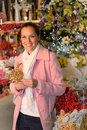 Smiling woman shopping xmas decorations in shop with basket Royalty Free Stock Image