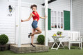 Smiling woman in shorts poses next to simple entrance door of country house Royalty Free Stock Photography