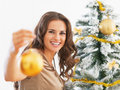 Smiling woman showing christmas ball near christmas tree portrait of young Stock Images