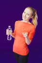 Smiling woman showing the index finger at the camera while holding a sign water bottle standing on a blue background Royalty Free Stock Photo