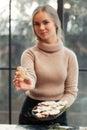 Smiling woman shows gingerbread man at camera