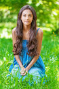 Smiling woman sits on green grass young charming dark haired in sundress in summer city park Stock Photos