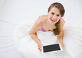 Smiling woman sitting in bed and using tablet PC Royalty Free Stock Images