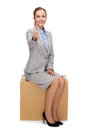 Smiling woman sitting on cardboard box Royalty Free Stock Photo