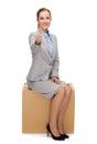 Smiling woman sitting on cardboard box Royalty Free Stock Photo