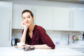 Smiling woman sitting and drinking tea on the kitchen Royalty Free Stock Photo