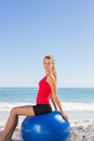 Smiling woman sitting on exercise ball looking at camera the beach Stock Image