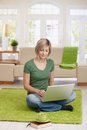 Smiling woman sitting on floor at home in living room using laptop computer for teleworking Stock Photography