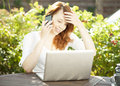 Smiling woman sitting in the garden using a mobile young redhead at wooden table front of her laptop computer chatting on her Stock Image