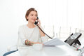 Smiling woman sitting in office and talking on telephone Royalty Free Stock Photo