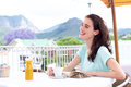 Smiling woman sitting at outdoor cafe with coffee and book Royalty Free Stock Photo