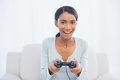 Smiling woman sitting on sofa playing video games in bright living room Stock Photos