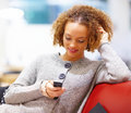 Smiling woman sitting on  sofa and text messaging Royalty Free Stock Photos
