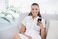 Smiling woman sitting on sofa using her phone in bright living room Royalty Free Stock Photography