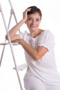 Smiling woman sitting on step ladder isolated white Stock Photos