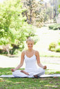 Smiling woman sitting in a yoga position in the park Royalty Free Stock Photo