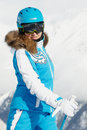 Smiling woman in ski suit poses against mountain Stock Photography