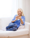 Smiling woman with smartphone at home technology and internet concept sitting on couch Royalty Free Stock Photography