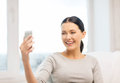Smiling woman with smartphone at home technology photography and internet concept taking picture of herself camera Royalty Free Stock Image