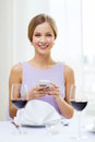 Smiling woman with smartphone at resturant reastaurant technology and happiness concept young and glass of red wine restaurant Stock Photo