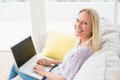 Smiling woman on sofa using laptop in living room side view of Stock Image