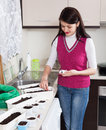Smiling woman sowing seeds in home kitchen Royalty Free Stock Photo