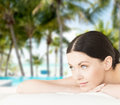 Smiling woman in spa salon vacation and resort concept lying on the massage desk Stock Photo