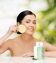 Smiling woman with sponge health spa and beauty concept and cosmetic bottles Royalty Free Stock Photos