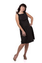 Smiling woman standing in a black dress and looking to the side. Royalty Free Stock Photo