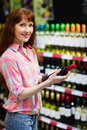 Smiling woman standing with a bottle of wine and posing Royalty Free Stock Photo