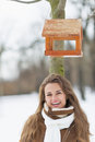 Smiling woman standing under bird feeder in winter park portrait of young Royalty Free Stock Photography