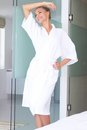 Smiling woman standing in white bathrobe Royalty Free Stock Photo