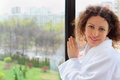 Smiling woman stands near window Stock Photos